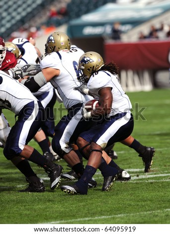PHILADELPHIA - OCTOBER 30: Akron running back Alex Allen (#10) runs behind his offesinsive linemen during a rush early in a game against Temple October 30, 2010 in Philadelphia