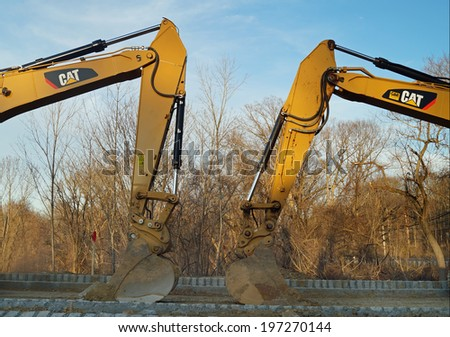 PHILADELPHIA, PA - April 6, 2014: Two CAT heavy equipment excavators face each other on a construction site in a new housing development.  - stock photo