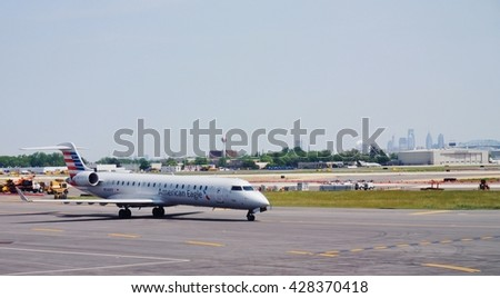 PHILADELPHIA, PA -25 MAY 2016- A Canadair regional jet airplane from American Eagle (AA) at the Philadelphia International Airport (PHL) with the Philly skyline in the background. - stock photo