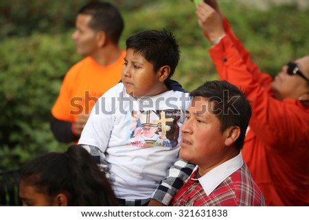 PHILADELPHIA, PA - SEPTEMBER 26 2015: Pope Francis celebrated mass at the Cathedral Basilica of Peter & Paul in downtown Philadelphia. Father holds son awaiting Pope's arrival - stock photo