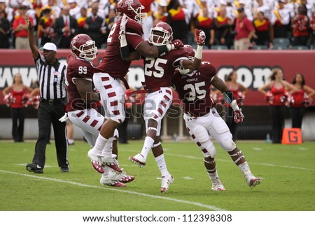 PHILADELPHIA, PA. - SEPTEMBER 8: Temple defenders celebrate a quarterback sack late in the game against Maryland on September 8, 2012 at Lincoln Financial Field in Philadelphia, PA. - stock photo