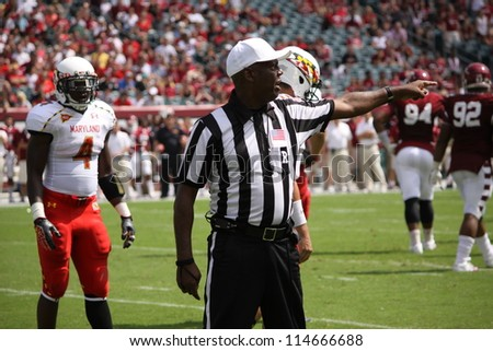 PHILADELPHIA, PA. - SEPTEMBER 8: The referee  signals a penalty against the defense during a game, Maryland against Temple on September 8, 2012 at Lincoln Financial Field in Philadelphia, PA. - stock photo