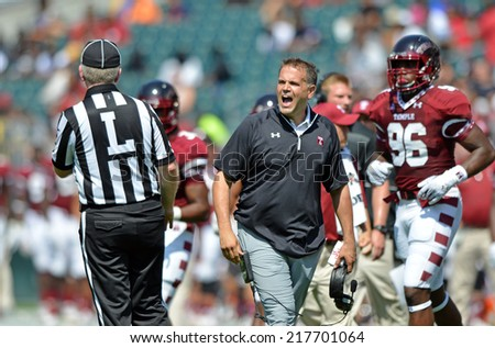 PHILADELPHIA - SEPTEMBER 6: Temple Owls head coach Matt Rhule (black shirt) shown in a NCAA football game between Temple and Navy September 6, 2014 in Philadelphia.  - stock photo