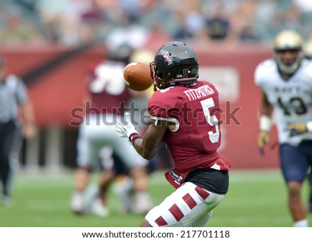 PHILADELPHIA - SEPTEMBER 6: Temple Owls wide receiver Jalen Fitzpatrick #5 looks in a pass during a NCAA football game between Temple and Navy September 6, 2014 in Philadelphia.  - stock photo