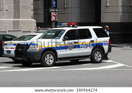 PHILADELPHIA, USA - JUNE 11, 2013: Unidentified person walks by Philadelphia Police Ford Explorer. Philadelphia Police Department is the oldest city police agency in the US (formed 1751). - stock photo