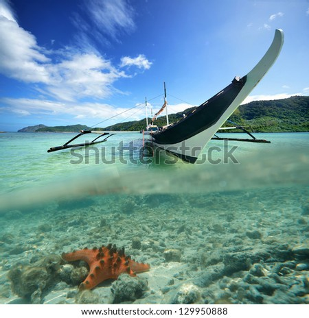 Philippine original boat on a background of green islands and starfish in the foreground. - stock photo