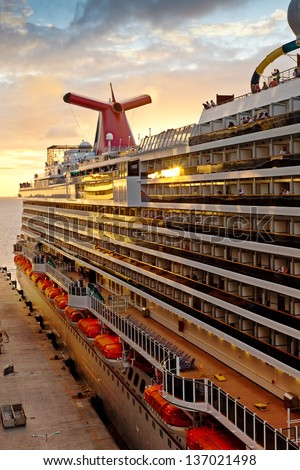 PHILIPSBURG, ST. MAARTEN - JAN. 16:  Carnival's Dream ship gets ready for departure at sunset on Jan. 16, 2013.  The ship is one of Carnival's largest ships, one of three in the line of Dream-classes. - stock photo