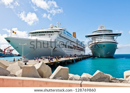 PHILIPSBURG, ST. MAARTEN - JAN.16: Cruise ships docked on the Dutch side of St. Maarten on Jan. 16, 2013.  Philipsburg is one of the busiest islands as the port can accommodate half dozen ships. - stock photo