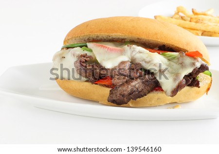 Philly cheese steak sandwich served with a side of fries - stock photo