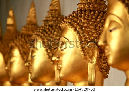PHITSANULOKE-THAILAND-OCTOBER 19 : A row of golden Buddha statue in Thai temple, Buddha is the worship of Thai Buddhist on October 19, 2013, Phitsanuloke Province, Thailand
