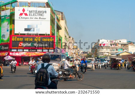 PHNOM PENH, CAMBODIA - FEBRUARY 27, 2014: A busy intersection in the Cambodian capital has traffic moving in many directions under bold signs of booming economic activity. - stock photo