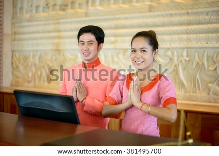PHNOM PENH, CAMBODIA - JANUARY 2015: A charming Cambodian couple in Khmer traditional costume gesturing or Chumreap sour - Khmer greeting and farewell manner at Phnom Penh hotel in Cambodia. - stock photo