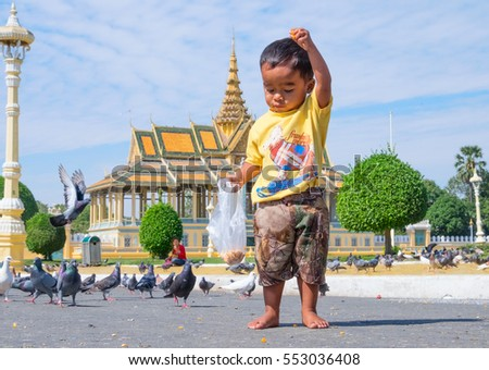 PHNOM PENH, CAMBODIA - JANUARY 5, 2015:  A small child in front of a Buddhist temple