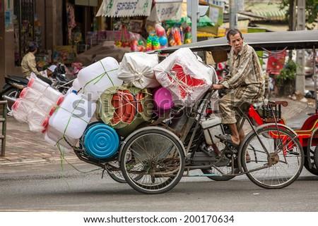 PHNOM PENH, CAMBODIA - MARCH 21: Plastic ware vendor driving his bicycle in Phnom Penh, Cambodia on March 21, 2014 - stock photo