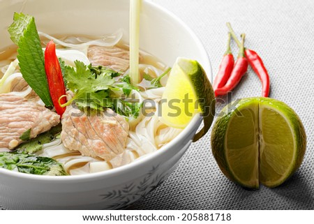 Pho bo soup with lime and chili over the gray surface closeup