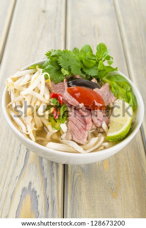 Pho Bo - Vietnamese fresh rice noodle soup with beef, herbs and chili topped with chill and hoisin sauce Vietnam's national dish. - stock photo