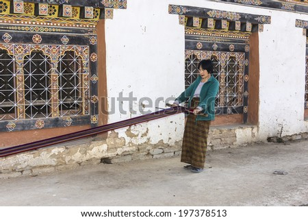 PHOBJIKHA VALLEY, BHUTAN - MARCH 03, 2014: woman weaving at gangtey village. It is a beautiful village with a well known monastery in Bhutan
