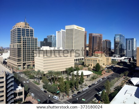 PHOENIX, AZ - FEBRUARY 4, 2016: Sunny winter day and clear sparkling blue sky above busy streets and tall skyscrapers in capital city of Phoenix, Arizona - stock photo