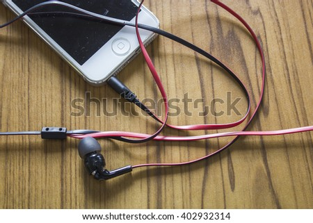 Phone and ear phone on wooden background