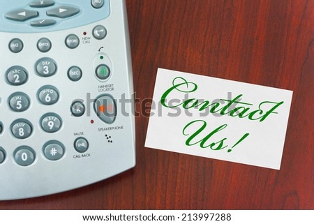 Phone and paper card Contact Us on wooden table - stock photo