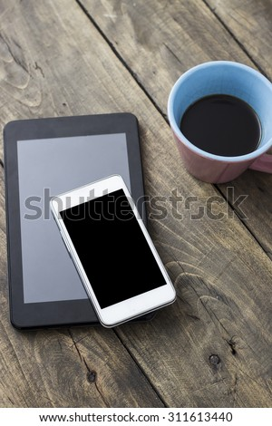 phone and tablet pc on wooden desk, from above - stock photo