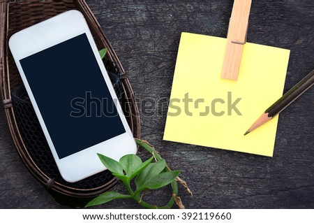 phone, blank note paper on wood desk top view. empty space for text. selective focus. - stock photo
