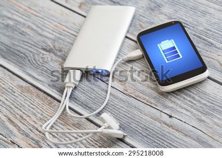 Phone charging with energy bank. - stock photo