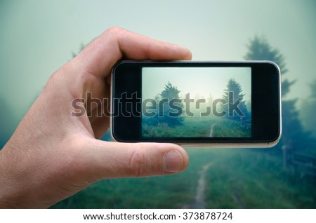 phone in hand man (photographing the landscape) photos from your phone, Self, photographing on the phone, the man photographs the mountain landscape on the phone (smartphone) - stock photo