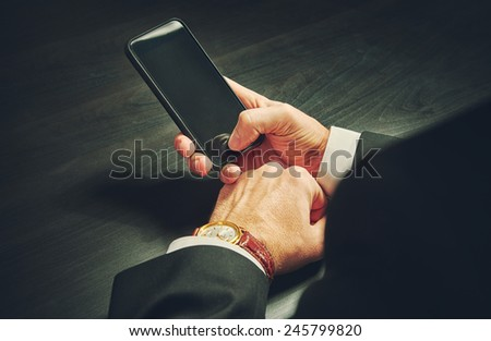 phone in the hands of a businessman in dark colors - stock photo