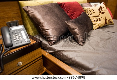 Phone on a table near a bed. - stock photo