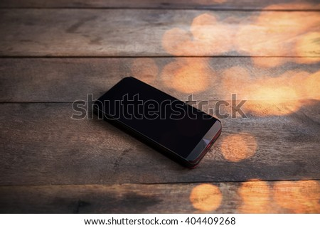 Phone on table with refection bokeh background (Concept Finance and investment) - stock photo