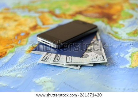 Phone, passport, money on a background map of the world. Traveling concept - stock photo