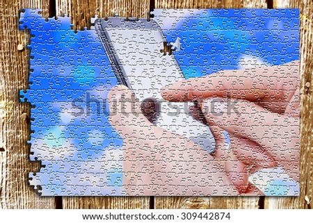 Phone tablet in hand, background puzzles - stock photo