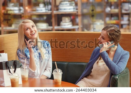 Phone talks. Two smiling cheerful girls talking over the phone while they sit in a caf�© in shopping mall and drink milk cocktails - stock photo