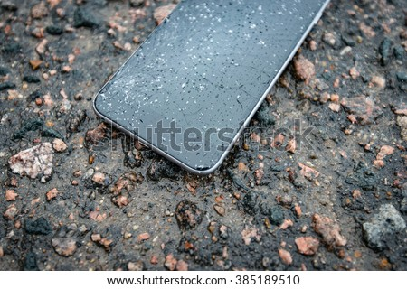 Phone with broken screen on asphalt. Someone dropped device. Glass covered with snow flakes. - stock photo