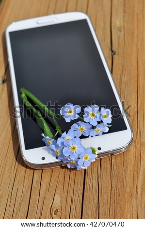 Phone with forget-me-not flower on the wood. Space for text. - stock photo