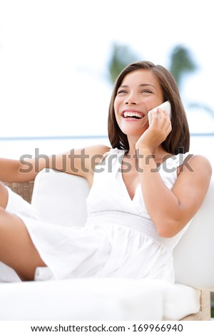 Phone woman talking on phone. Relaxed mixed race model sitting on sofa laughing and happy smiling and relaxing. Asian Caucasian girl in her 20s. - stock photo