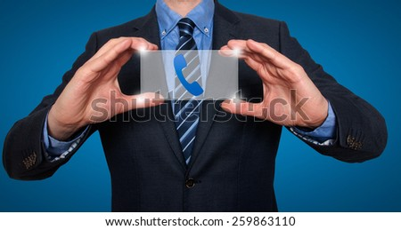 Phonel and contact symbols in front of businessman. Blue background - Stock Image - stock photo