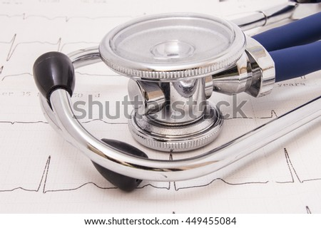Phonendoscope and stethoscope with chrome binaural pieces and blue flexible tubing lies on the electrocardiogram (EKG or ECG) large chest piece upwards - stock photo