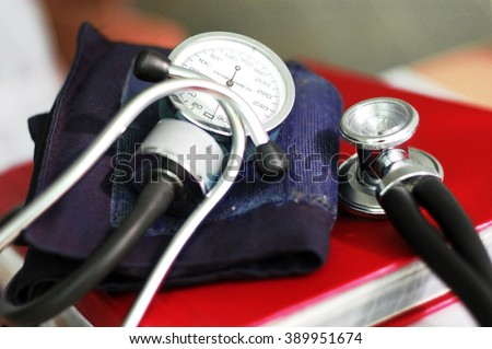 phonendoscope and tonometer on the red notebook - stock photo