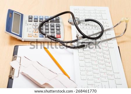 phonendoscope, white keyboard, calculator, ECG and blank clipboard on table - stock photo