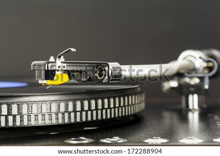 Phonograph cartridge waits to start playing music - stock photo