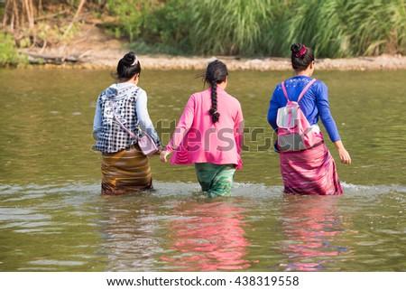 PHOP PHRA, TAK, THAILAND - MAY 10, 2016 : Three young Karen woman are walking across the Moei river at Ban Mun Ru Chai, Phop Phra, Tak, Thailand. - stock photo