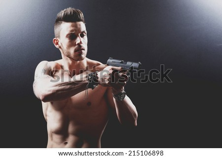 photo a young man drawing a gun in self defense studio shoot .Fashion colors.  - stock photo