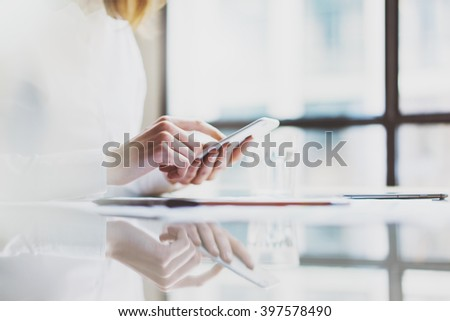 Photo account manager working new startup project modern office.Contemporary smartphone holding female hands and texting message.Glass water.Horizontal, film effect. Blurred windows background - stock photo