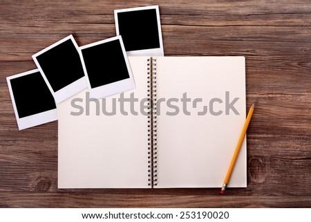 Photo album with blank polaroid style instant photo prints.   - stock photo