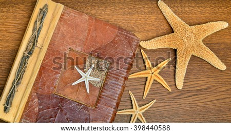 Photo album with starfish on a wooden table.