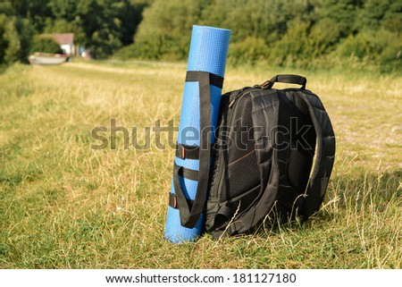 Photo backpack standing in a green  grass with blue yoga mat - stock photo