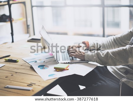 Photo bearded businessman working with new project modern loft. Generic design notebook on wood table.  Analyze plans, papers, hands texting keyboard. Blurred background, film effect - stock photo