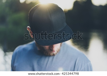 Photo Bearded Young Man Wearing Black Blank Cap. Green City Park Lake Background and Sunset effect. Front view. Horizontal Mockup. - stock photo